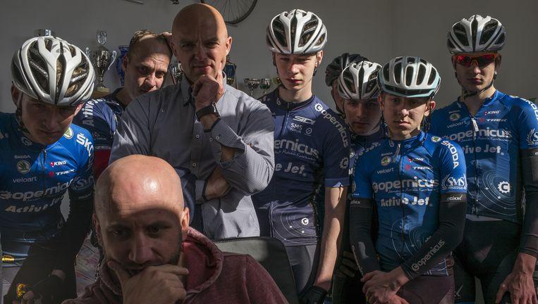 Leerlingen van de Poolse wielerschool Copernicus kijken met directeur Michal Jackowiak (voorgrond) en trainer Marcin Mientki naar beelden van de door Michal Kwiatkowski gewonnen Amstel Gold Race. Beeld Rigamonti