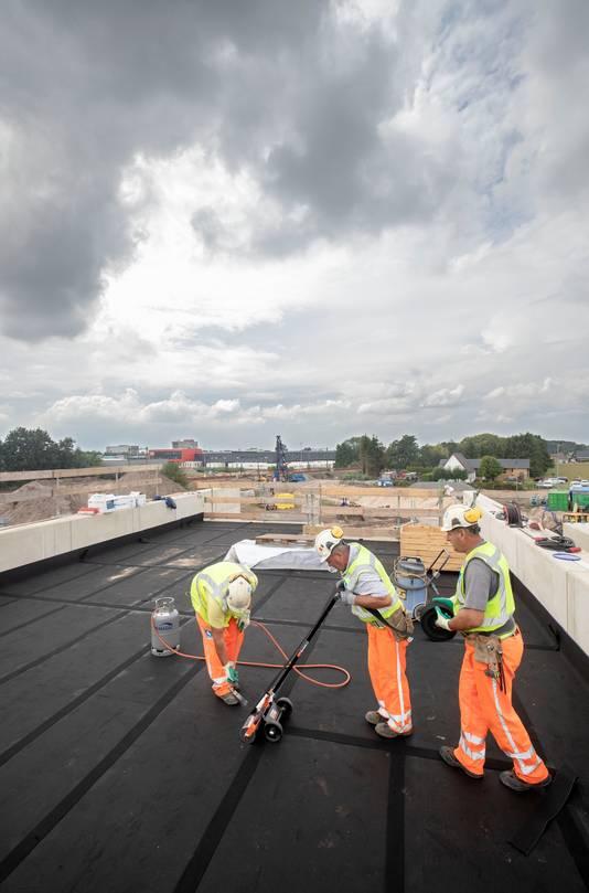 De mat wordt aangelegd voor het grind in de bak waar sporen komen te liggen.