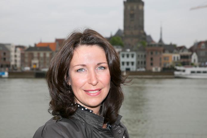VVD-gedeputeerde Monique van Haaf, met op de achtergrond haar woonplaats Deventer.