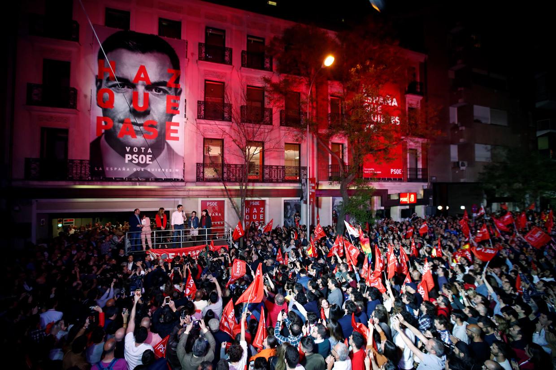 Aanhangers van de socialistische arbeiderspartij (PSOE) van Sánchez volgen de verkiezingsuitslag buiten het partijhoofdkwartier in Madrid, 28 april 2019. Beeld EPA