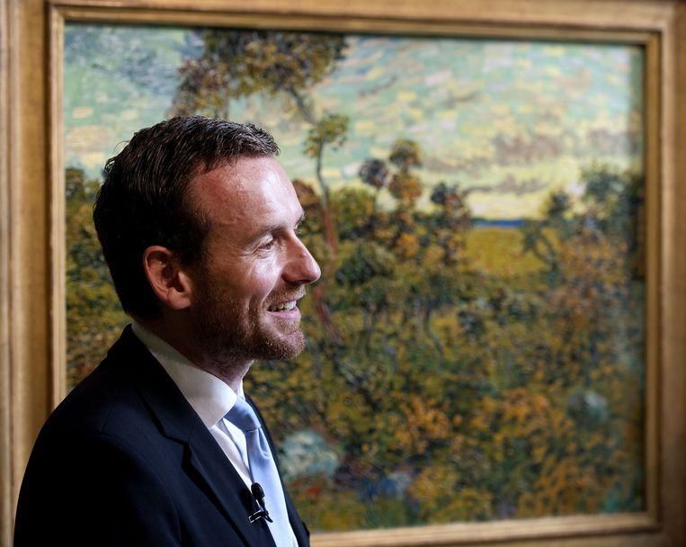 Axel Rüger. Op de achtergrond het zojuist onthulde nieuwe schilderij van Vincent van Gogh. Het gaat om het werk Zonsondergang bij Montmajour uit 1888. Beeld Olaf Kraak