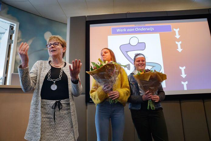 Scholieren van het Munnikenheide College en de KSE werden uitgedaagd een logo te ontwerpen voor het project Werk aan Onderwijs. Bij de Rabobank in Etten-Leur werd de winnaar bekend gemaakt. Isa Wouters en Mirre van de Ven van de KSE winnen de prijs. Links burgemeester Miranda de Vries.