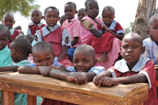 Blije kinderen bij de houten schoolbankjes.