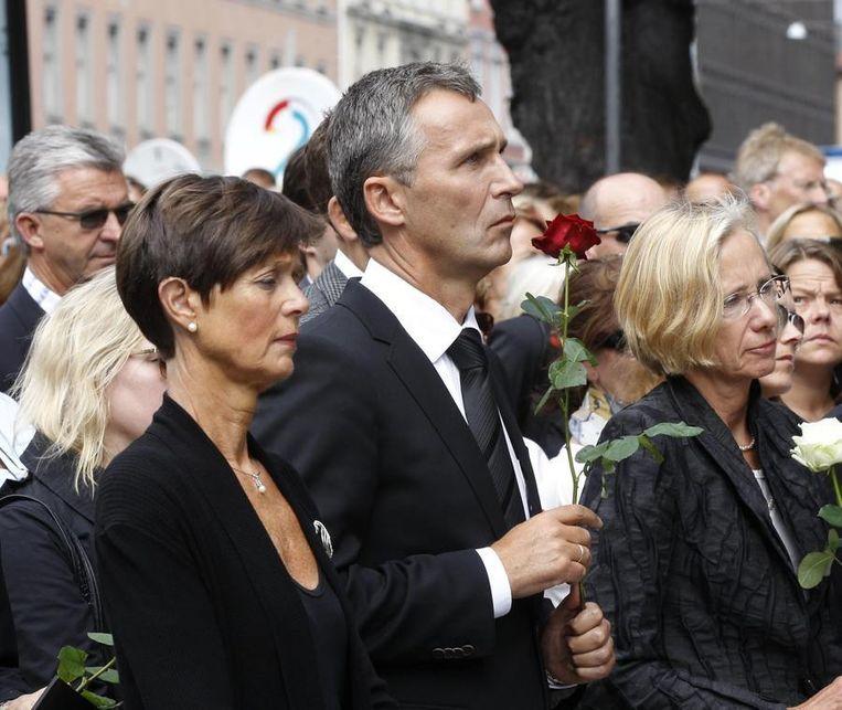 De Noorse premier Jens Stoltenberg (midden) en andere vertegenwoordigers van het Noorse parlement leggen in Oslo bloemen neer voor de slachtoffers van de aanslagen. Beeld reuters