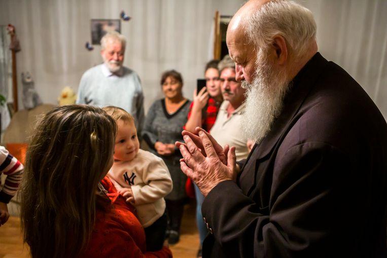 Predikant Gábor Iványi tijdens zijn bezoek aan het gezin in het Roma-dorp Gyöngyöspata. Beeld Julius Schrank