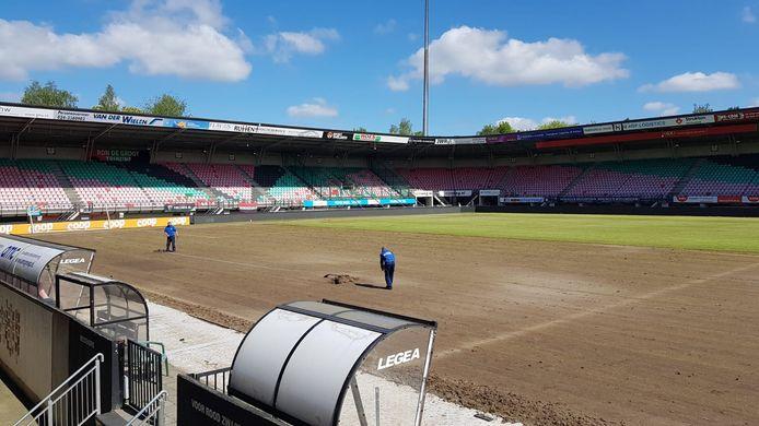 Medewerkers van NEC aan het werk op het veld in De Goffert dat al voor driekwart 'gestript' is.