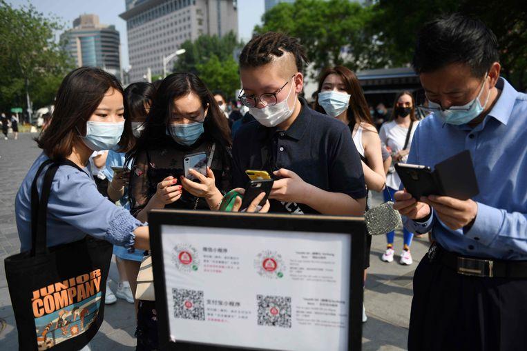 Mensen in China gebruiken een app om te bewijzen dat ze gezond zijn en mogen reizen in Peking.  Beeld AFP