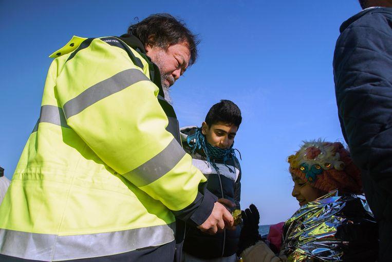 Ai Wei Wei op het strand van Lesbos met twee vluchtelingen. Beeld ap
