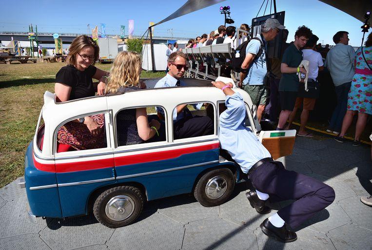 Bezoekers van het Democratiefestival. Met een alternatief pendelbusje kunnen ze van plek naar plek op het Waal-eiland Veur-Lent in Nijmegen. Beeld Marcel van den Bergh