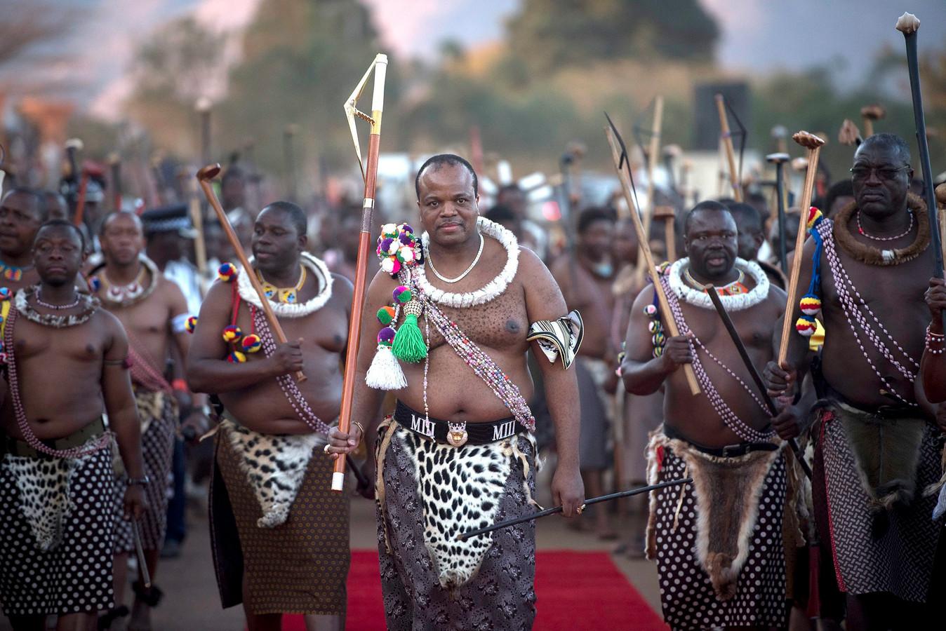 Koning Mswati III leidt de ceremonie op de jaarlijkse Rietdans waarbij ongehuwde en kinderloze vrouwen van het land vers gesneden riet aanbieden aan de vorst. Alleen meisjes en vrouwen die nog maagd zijn mogen meedoen. Foto EPA