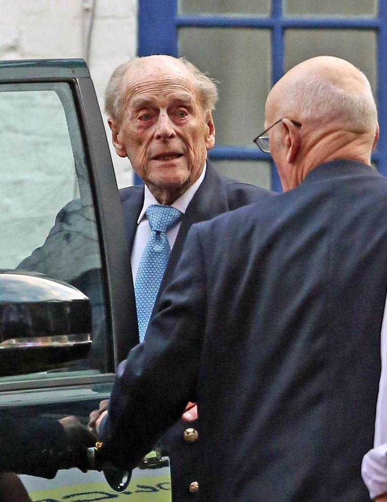 De Britse prins Philip verlaat het ziekenhuis in een auto.