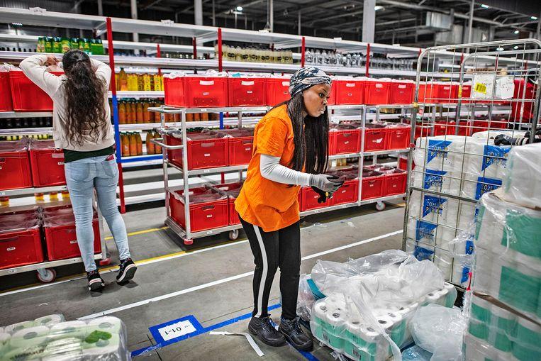 Personeel Picnic vult de kratten en dozen voor haar online klanten, alles wordt dubbel gescand.  Beeld Guus Dubbelman / de Volkskrant