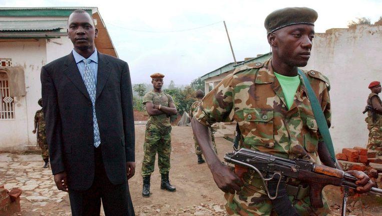 Thomas Lubanga in juni 2003 met bewapende manschappen van de Union des Patriotes Congolais bij zijn huis in Bunia. Beeld EPA