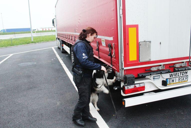 Een agente van de federale politie met een speurhond op zoek naar transmigranten.