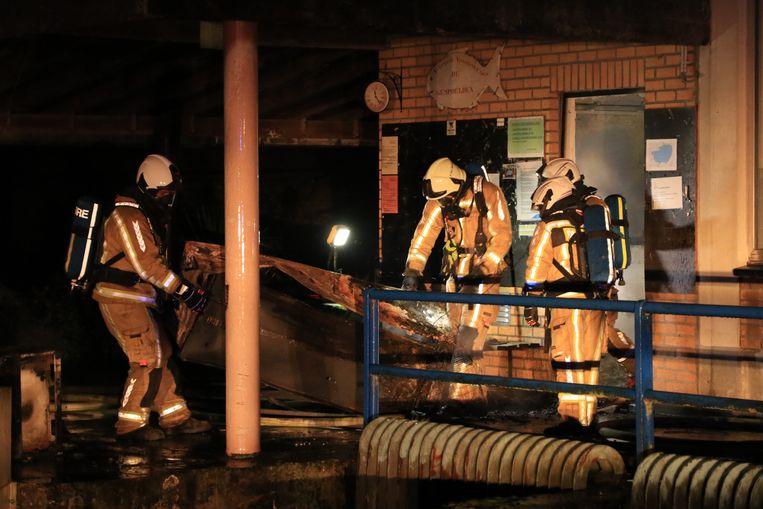 De brandweer bracht het uitgebrande materiaal naar buiten.