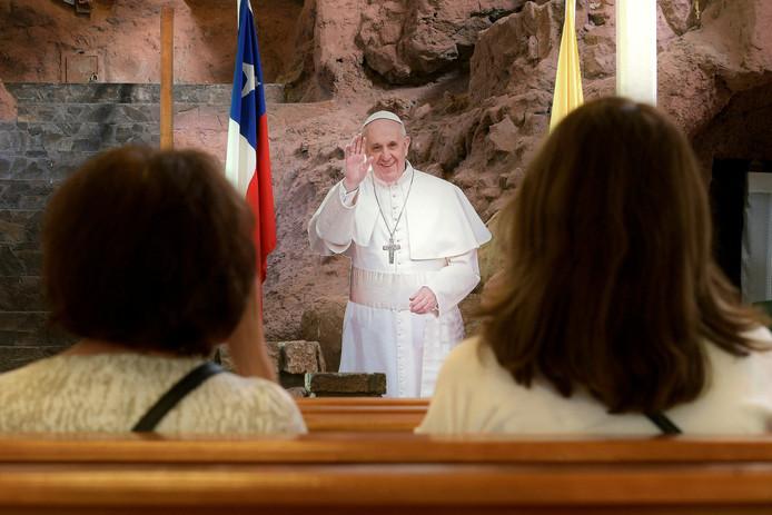 Twee gelovigen slaan een kruisje in de Chileense kerk in Iquigue terwijl Paus Franciscus hen vriendelijk toewuift. Deze paus is nog van karton. Komende maandag zal de paus in het echt een bezoek brengen aan Chili. Foto Cristian Vivero