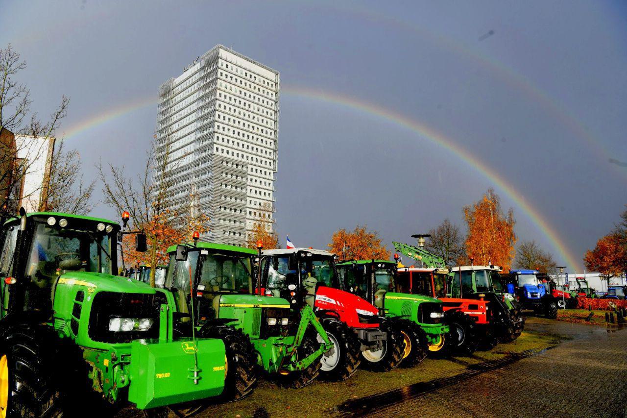Een regenboog boven de geparkeerde tractors verschijnt tijdens het boerenprotest bij waterschap Vallei en Veluwe in Apeldoorn.