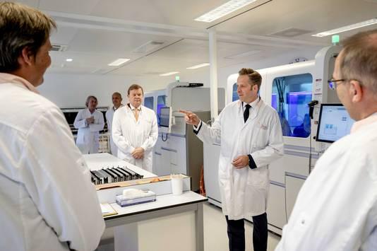 Minister Hugo de Jonge (zwarte das) en speciaal coronagezant Feike Sijbesma (beige das) krijgen een rondleiding bij Sanquin.