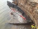 Een van de eerder gevonden middeleeuwse schepen nog half in het water en in het zand.