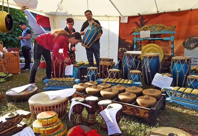 Showroom Indonesische muziekinstrumenten op garagesale Sluiskil. Verkoopster Suus (midden) bezig met potentiële klanten.