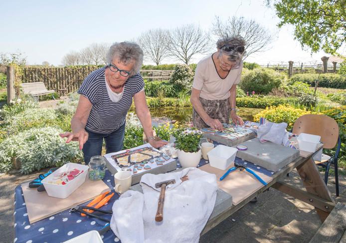 Paula van Garsel (links) en Catrien Tax zijn buiten druk in de weer met hun mozaïektegels.