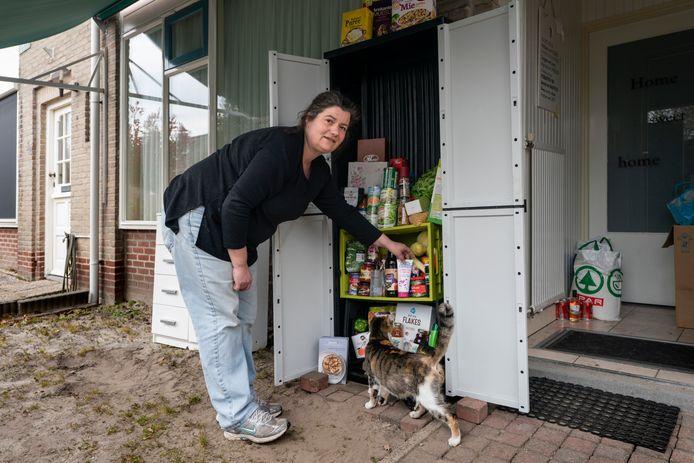 Karin Flisijn uit Schijndel bij de Neem-geef-kast in haar voortuin. De producten in deze kast zijn bedoeld voor minima tijdens de coronacrisis.