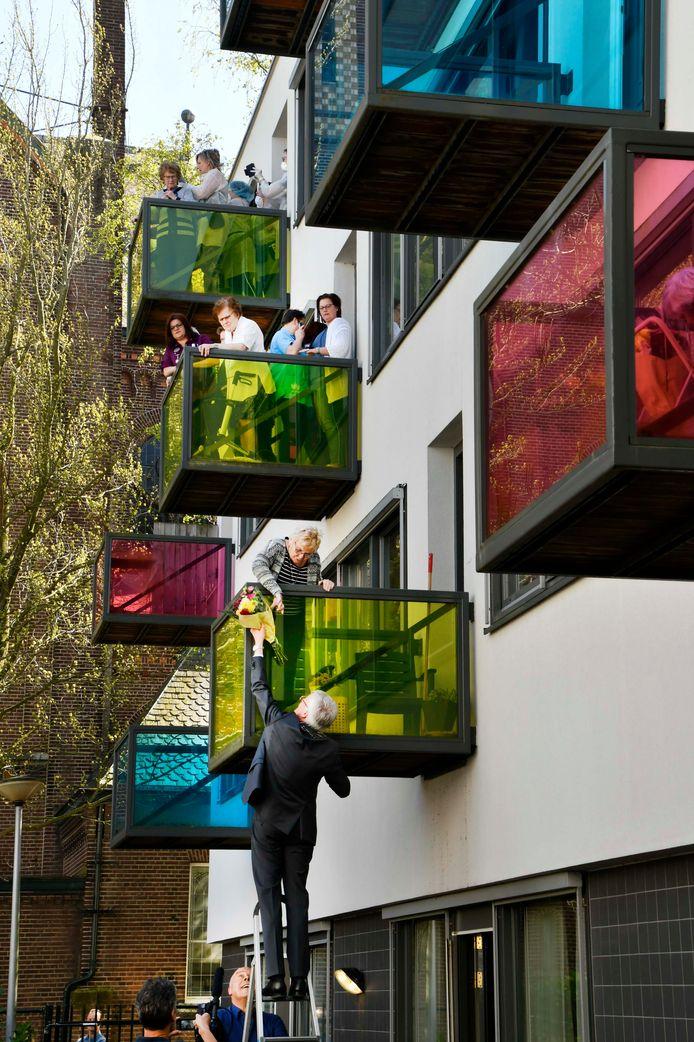 Burgemeester Theo Weterings klautert op een iel trapje om bloemen over de balkonrand heen aan te reiken. Even later duikt ook Ali B op: de rapper en burgervader mogen elkaar.