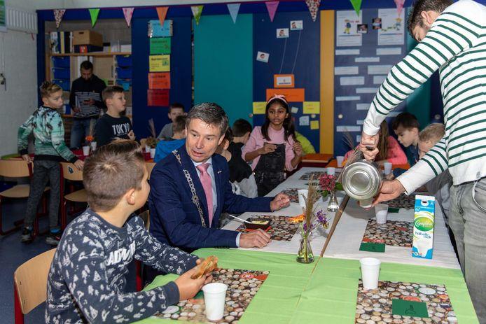 Burgemeester Huub Hieltjes van Kapelle ontbijt samen met de kinderen van groep 5/6 van CBS de Hoeksteen in Wemeldinge. Meester Michael Tramper schenkt de thee in.