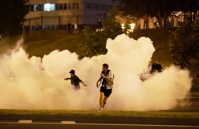Demonstranten rennen weg nadat de politie verdovingsgranaten afvuurt in Minsk.