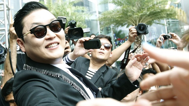 Psy schudt handen in Bangkok.