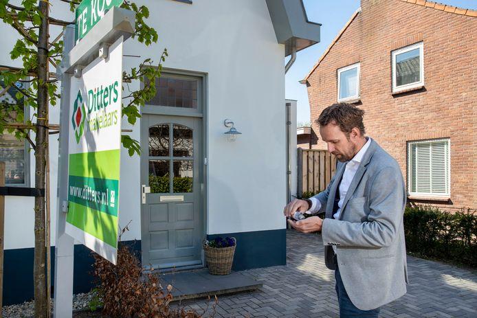 Makelaar Ron Toering desinfecteert zijn handen voor hij een te verkopen woning in Bennekom binnengaat.