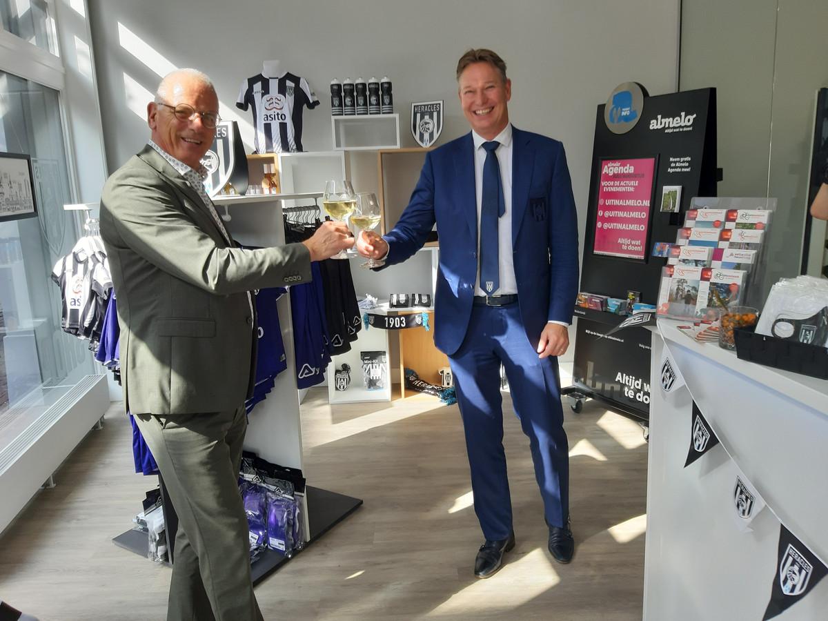 Directeur Rob Toussaint van Heracles (r) heft het glas met wethouder Jan Martin van Rees in de net geopende fanshop van de profclub in de Almelose binnenstad.