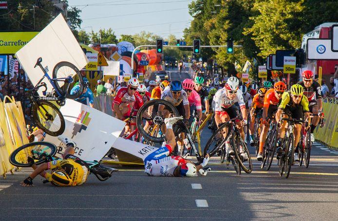 Dylan Groenewegen (l) ligt op de grond na de valpartij die hij heeft veroorzaakt in de Ronde van Polen.