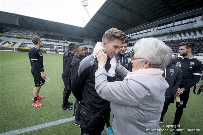 Jo Evers doet middenvelder Peter van Ooijen de door haarzelf gebreide das om.