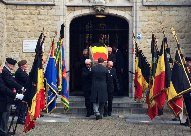 De kist van Alfons Saenen wordt de kerk buiten gedragen terwijl oud-strijders een erehaag vormen.
