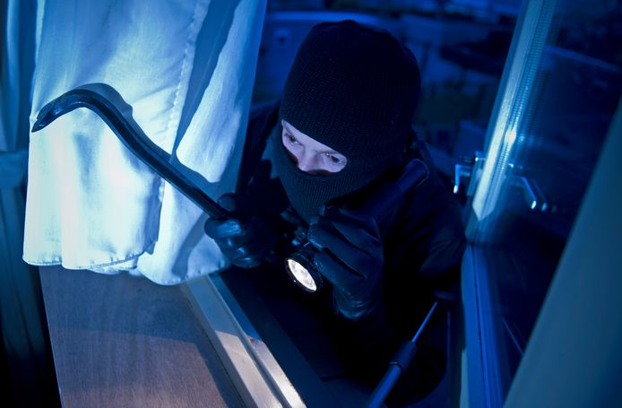Een inbreker probeert ergens binnen te komen.