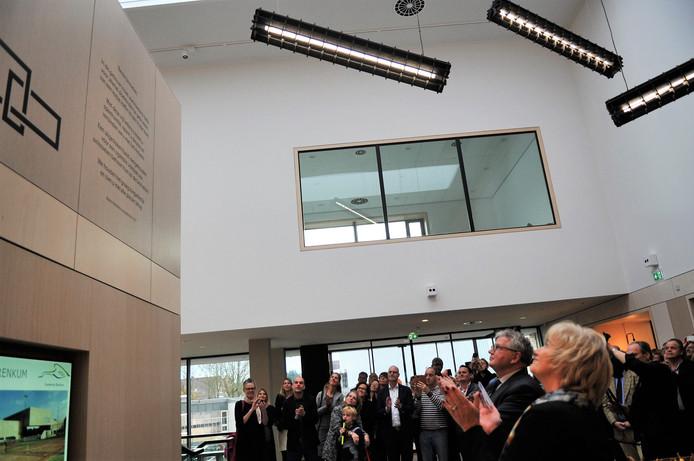 Burgemeester Schaap en Jos Buijs kijken op naar het gedicht van dorpsdichteres Bianca Hendriks.