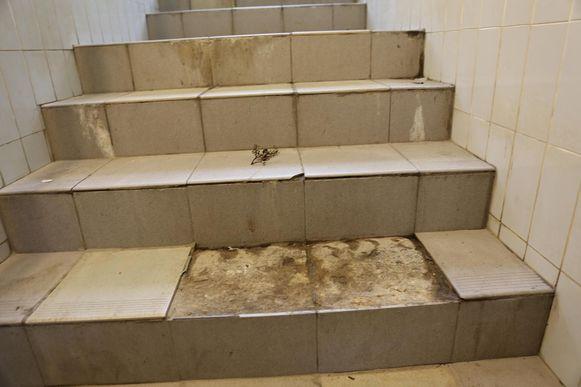 De tegels van de trap naar de reizigerstunnel brokkelen af of zijn verdwenen.