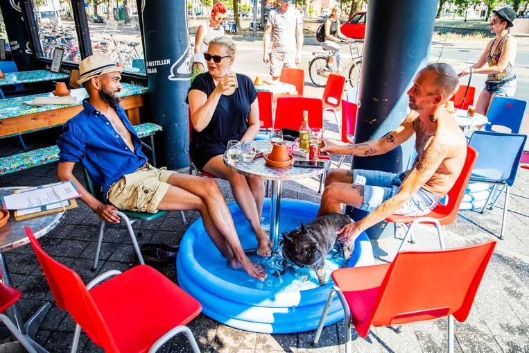Bezoekers van een cafe zitten met hun voeten in een zwembadje op een terras aan de Nassaukade in Amsterdam. Beeld ANP