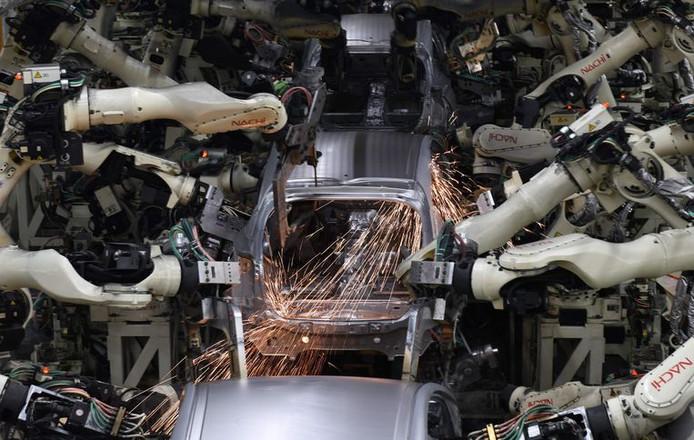 Robotarmen bezig met laswerkzaamheden aan een Toyota Prius.