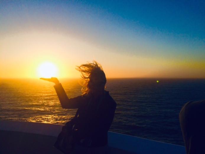 De zon niet in het haar, maar in de hand. Een bijzondere zonsondergang bij Cabo São Vincento in Portugal. Je moet maar net een camera bij je hebben.