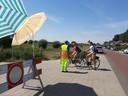 De verkeersregelaar langs de Veerweg legt twee meiden de regels uit. Zij mochten doorrijden omdat ze lid zijn van de waterscouts.