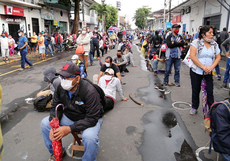 Mensen drommen samen in de rij voor de bank in de Peruaanse stad Iquitos om hun overheidssteun in ontvangst te kunnen nemen. Beeld AFP