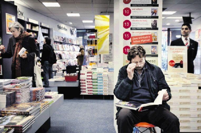 Steven de Waal (54), leest in 'Mensenwerk' van Ruud Koole, op een kruk in de boekhandel. ( FOTO WERRY CRONE ) Beeld