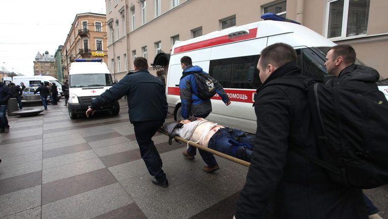 Een gewonde man wordt afgevoerd bij een metrostation in het centrum van Sint-Petersburg, waar een bomexplosie heeft plaatsgevonden. Beeld afp