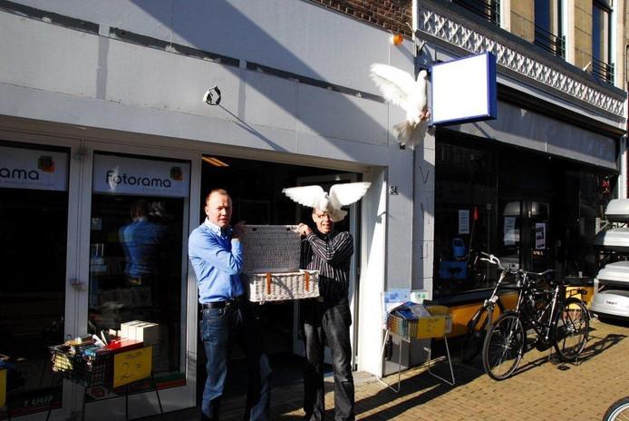 Eigenaar van Fotorama Kampen, Jan Willem Genuit (rechts) laat samen met een leverancier duiven los. Foto: Wilfred Hamelink