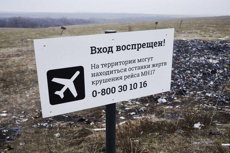 Een bord waarschuwt passanten dat vanaf hier de crashsite van vlucht MH17 begint. Beeld anp