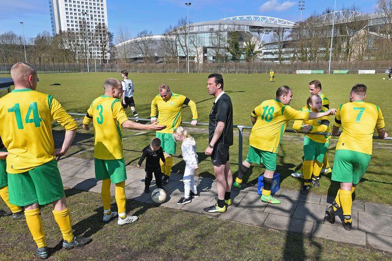 Spelers van Domstad Majella 5 praten met de scheidsrechter is de pauze van de wedstrijd tegen Maarssen 5, de voetballers van Majella spelen met een rouwband. Beeld Guus Dubbelman / de Volkskrant