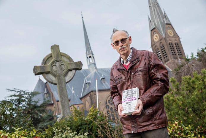 Frank de Klerk voor de Bartholomeuskerk in Poeldijk met in zijn hand het boek van de commissie-Deetman.