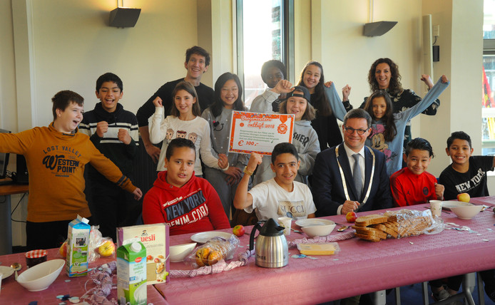 De Vlissingse burgemeester Bas van den Tillaar ontbeet donderdagmorgen met leerlingen van groep 8 van openbare basisschool Ravenstein. Jim houdt de cheque voor de Stichting Kinderpostzegels omhoog.